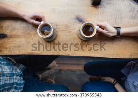 Top view of two cups on the table in cafe holded by hands of young couple  - stock photo