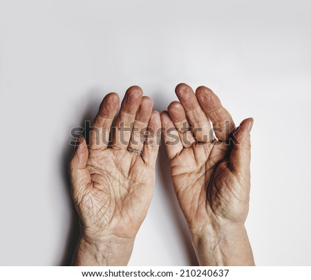 Top view of two empty female hands over grey background. Senior woman hands pleading. Wrinkled palms of aged woman with copy space. - stock photo