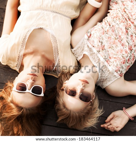 top view of two pretty young girls in summer dresses and sunglasses hold hands lying on wooden bridge - stock photo
