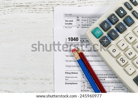 Top view of U.S. Individual tax form 1040 with old calculator and pencils on wooden desktop  - stock photo