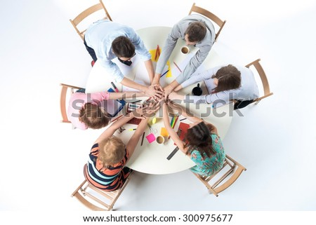 Top view of united hands of business team, sitting at a round table on white background  - stock photo