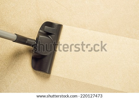 Top View of Vacuum Cleaner sweeping Brand New Carpet, Housework and home hygiene. - stock photo