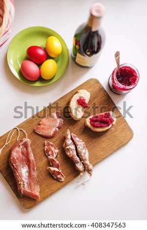 Top view of various meats on serving board. Ham, pork, beef, red wine, easter eggs and homemade bread with beetroot-horseradish spread. Preparing for dinner to celebrate Easter. Selective focus - stock photo