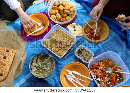 Top view of various picnic food: vegetable and feta salad, baba ghanoush, healthy crackers, rice fritters and olive bread. - stock photo