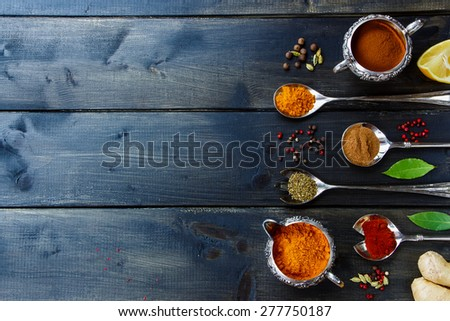 Top view of Various powder spices in old metal cups and spoons over dark wooden table. Background with space for text, food or cooking concept.  - stock photo