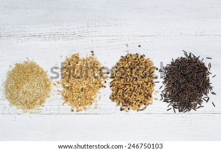 Top view of various rice types each within an individual pile on white wood - stock photo