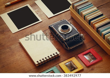 top view of vintage camera and old slides frames over wooden table background  - stock photo