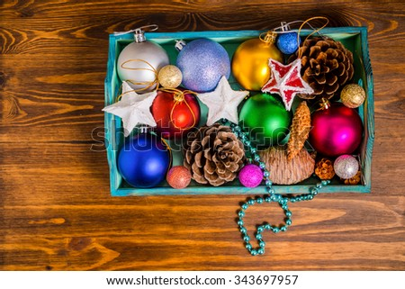 top view of vintage wooden box with Christmas decoration, tinsel,  pinecones, stars and balls on wooden background, closeup  - stock photo