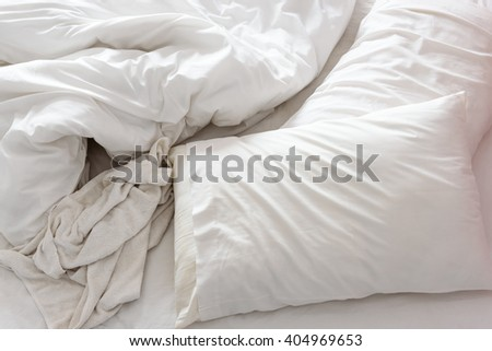 Top view of white bedclothes that are not neatly arranged for new customers / guest to sleep in. Including a shower towel, two pillows and a blanket. A shot with natural light through a room window. - stock photo