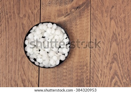 Top view of white cosmetic beeswax pellets in a black container on a wooden table. - stock photo