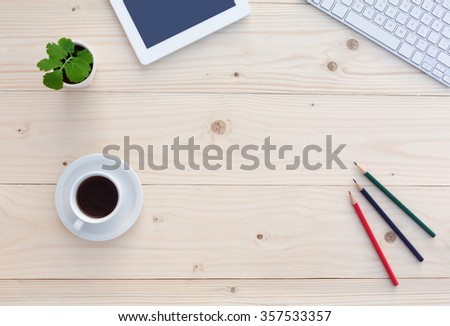 Top View of White Office Desk with Modern Electronics Computer Keyboard Tablet Notepad Color Pencils Coffee Cup and Green Flower - stock photo
