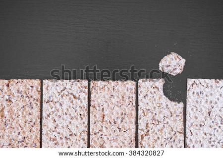 Top view of whole grain crispy crackers with seeds on a black wooden table. - stock photo