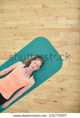 Top view of woman relaxing on yoga mat with copy space. Fitness female lying on exercise mat at gym. - stock photo