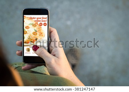 Top view of woman walking in the street using her mobile phone to order food online with copy space. All screen graphics are made up. - stock photo