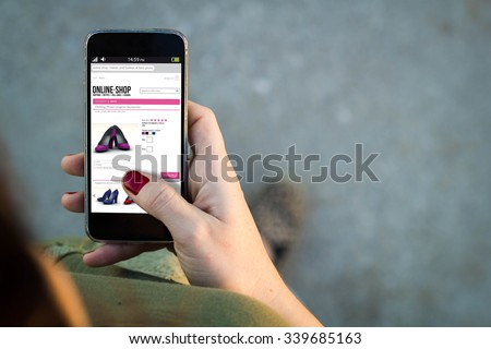 Top view of woman walking in the street using her mobile phone with online shop in the screen with copyspace. All screen graphics are made up. - stock photo