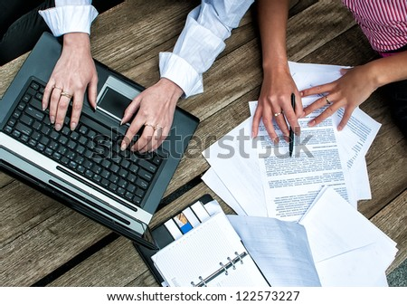 Top view of women's hands with documents and laptop - stock photo