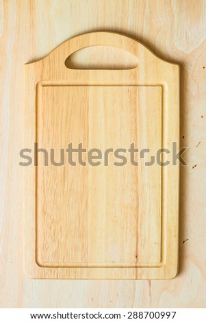 Top view of wooden cutting board on wooden table - stock photo