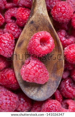 Top view of wooden spoon with some raspberries on it. - stock photo