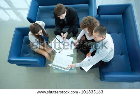 Top view of working business group sitting at table during corporate meeting - stock photo