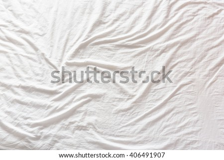 Top view of wrinkles on an unmade bed sheet after waking up in the morning. - stock photo