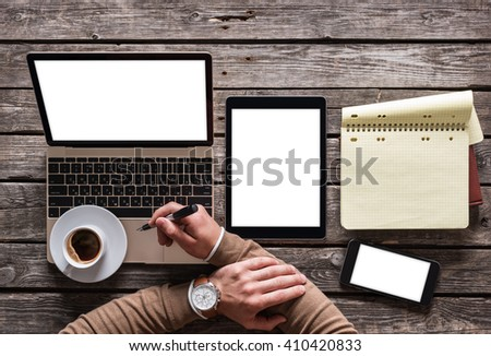 Top view of writer's workplace - laptop, tablet pc, smart phone and a cup of coffee. Clipping paths included. - stock photo