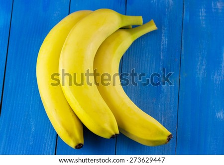 Top view of yellow bananas on blue wooden background - stock photo