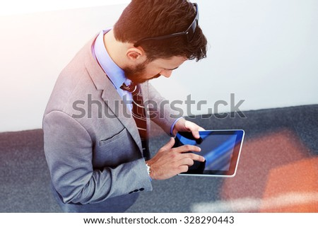 Top view of young business man or manager using touch pad to prepare for work day while standing in modern office interior, skilled male dressed in luxury suit working on digital tablet before meeting - stock photo