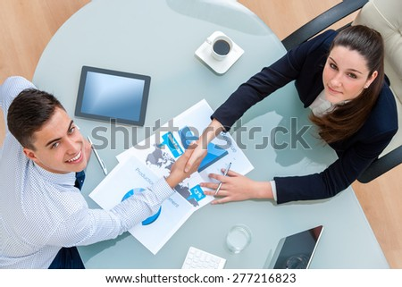Top view of young Business partners closing a deal.Couple shaking hands over deal with documents and digital tablet on table showing statistics and graphics. - stock photo
