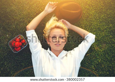 Top view of young charming female enjoying rest after strolling while lying down on the green grass in sunny summer day, pretty blonde hair woman with trendy hat and box of strawberries posing in park - stock photo