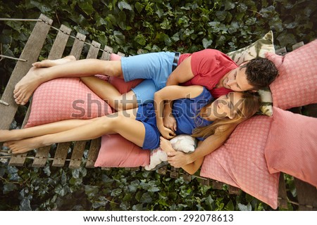Top view of young couple lying on a garden hammock. Young man embracing his girlfriend relaxing in backyard garden. - stock photo