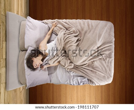 top view of young female in bed unable to sleep - stock photo