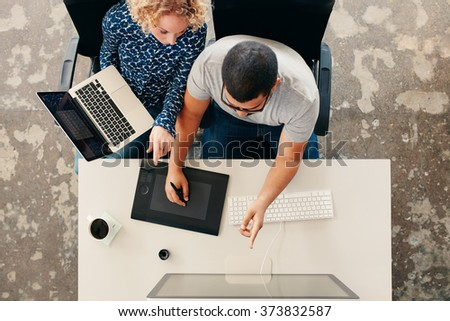 Top view of young graphic designers working together in office. Using digitized graphic tablet, digitized pen and desktop computer. Man showing his work on monitor to woman with a laptop. - stock photo