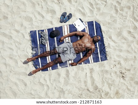 Top view of young guy lying shirtless on a mat sunbathing. African male model relaxing on beach on a hot summer day. - stock photo