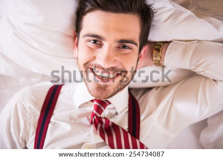 Top view of young handsome man is looking at the camera and smiling. - stock photo