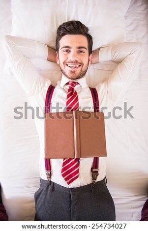 Top view of young handsome man is sleeping on bed in suit. - stock photo