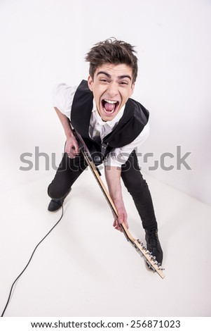 Top view of young male musician is playing a six-string bass guitar in studio. - stock photo