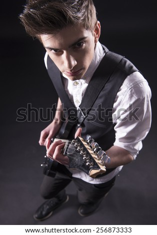 Top view of young male musician is playing a six-string bass guitar isolated on dark background. - stock photo
