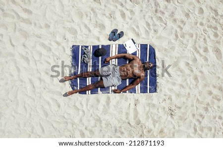 Top view of young man lying shirtless on a beach mat. African male model sunbathing. - stock photo