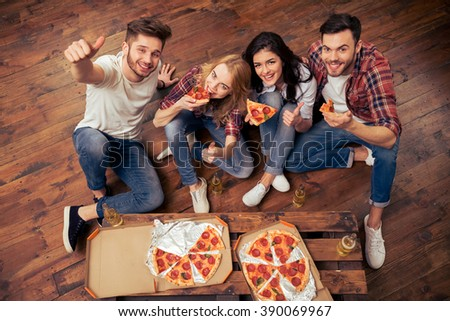 Top view of young people in casual clothes eating pizza, drinking and looking at camera. One guy is showing Ok sign - stock photo