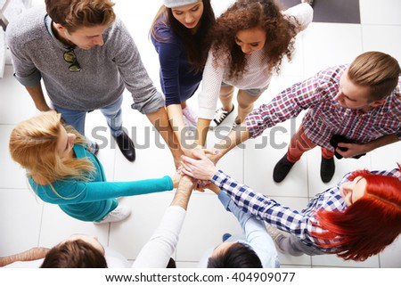 Top view of young people putting hands together - stock photo