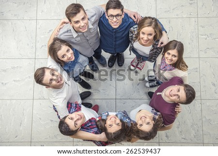 Top view of young people  together in a circle and looking at camera. - stock photo