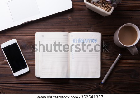 Top view office desk mockup: notebook, laptop, smartphone, snacks, and cup of coffee on rustic brown wooden background. New year resolution 2016 - stock photo