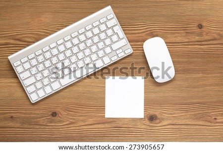 Top view office workplace - blank white notepad, keyboard and mouse on dark wooden background with copy space - stock photo
