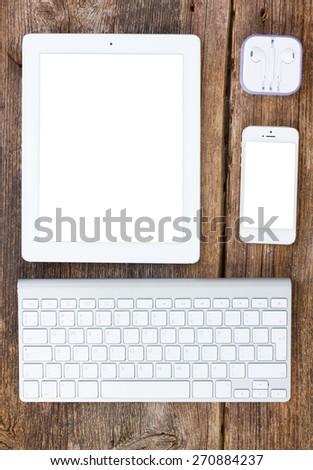Top view office workplace -  set of tablet, keyboard and phone on wooden background, copy space on screen - stock photo