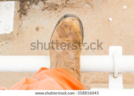 top view old work boots on steel pipe  - stock photo