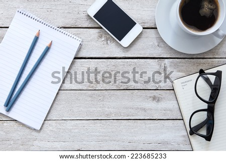 Top view on a table in the workplace with cup of coffee - stock photo