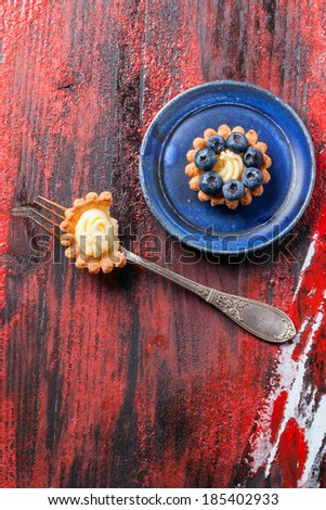 Top view on blueberry mini tart served on blue ceramic plate with vintage fork over black and red wooden background. - stock photo