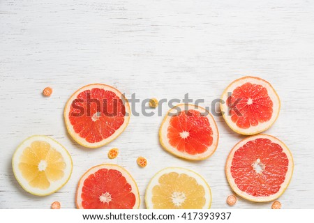 Top view on colorful cut grapefruit on white wooden background. Red and yellow citrus on white board with small candies. Flat lay - stock photo