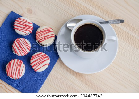 top view on decorated cookies on table with napkin and white cup with  black coffee - stock photo