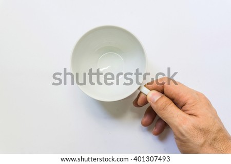 Top view on empty white coffee or tea mug or cup holding by man hand. Studio shot from above on white background./ Coating coffee cup on white background. - stock photo